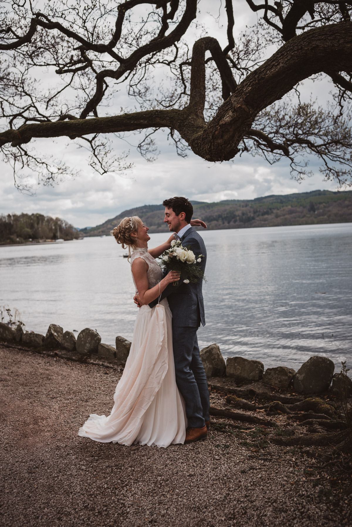 bride and groom in front of lake windermere district natural pose