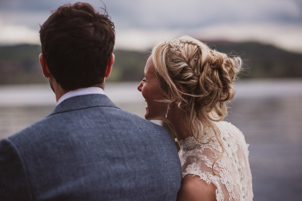 bride and groom in front of lake windermere district laughing