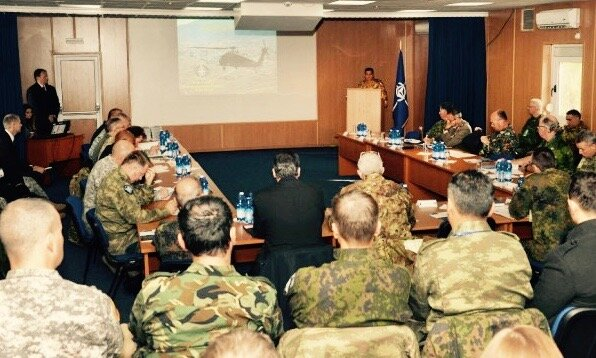 That's me standing on the left, hosting a conference with NATO in Kosovo (KFOR).