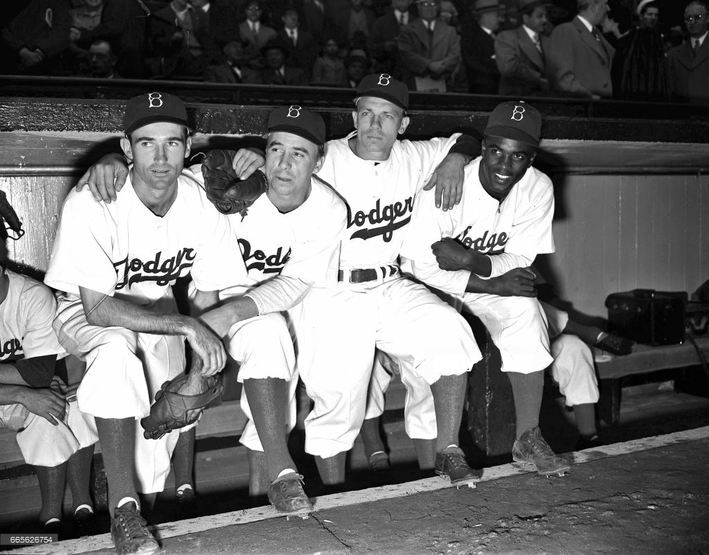 Dodger teammates pose with Jackie prior to the April 15, 1947 contest. L-R: Spider Jorgensen, Pee Wee Reese, Eddie Stanky, Robinson