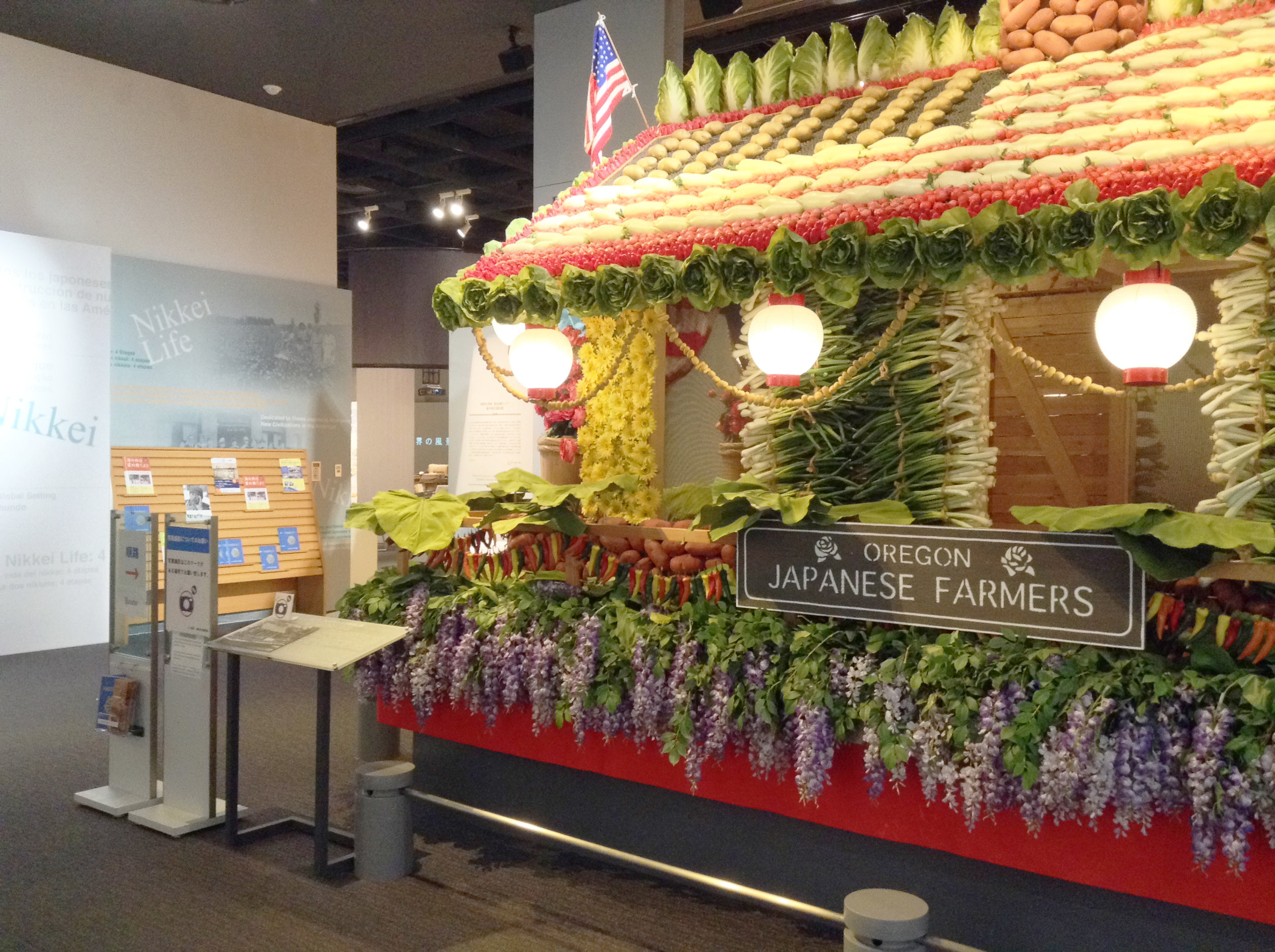 A scaled down replica of the Vegetable Float used in the Rose Parade at Japanese Overseas Migration Museum in Yokohama. It is a symbol of Nikkei communities working hard in the U.S. You can see an American flag made of crops on its roof. It is assumed that the Japan flag was on the other side.   PHOTO: ARISA NAKAMURA    海外移住資料館にあるオレゴン州のローズフェスティバルで使用された野菜山車のレプリカ。アメリカで仕事に励んだ日系人のシンボルである。山車の屋根には野菜でアメリカ国旗が描かれており、反対側には日本国旗があったと考えられている。