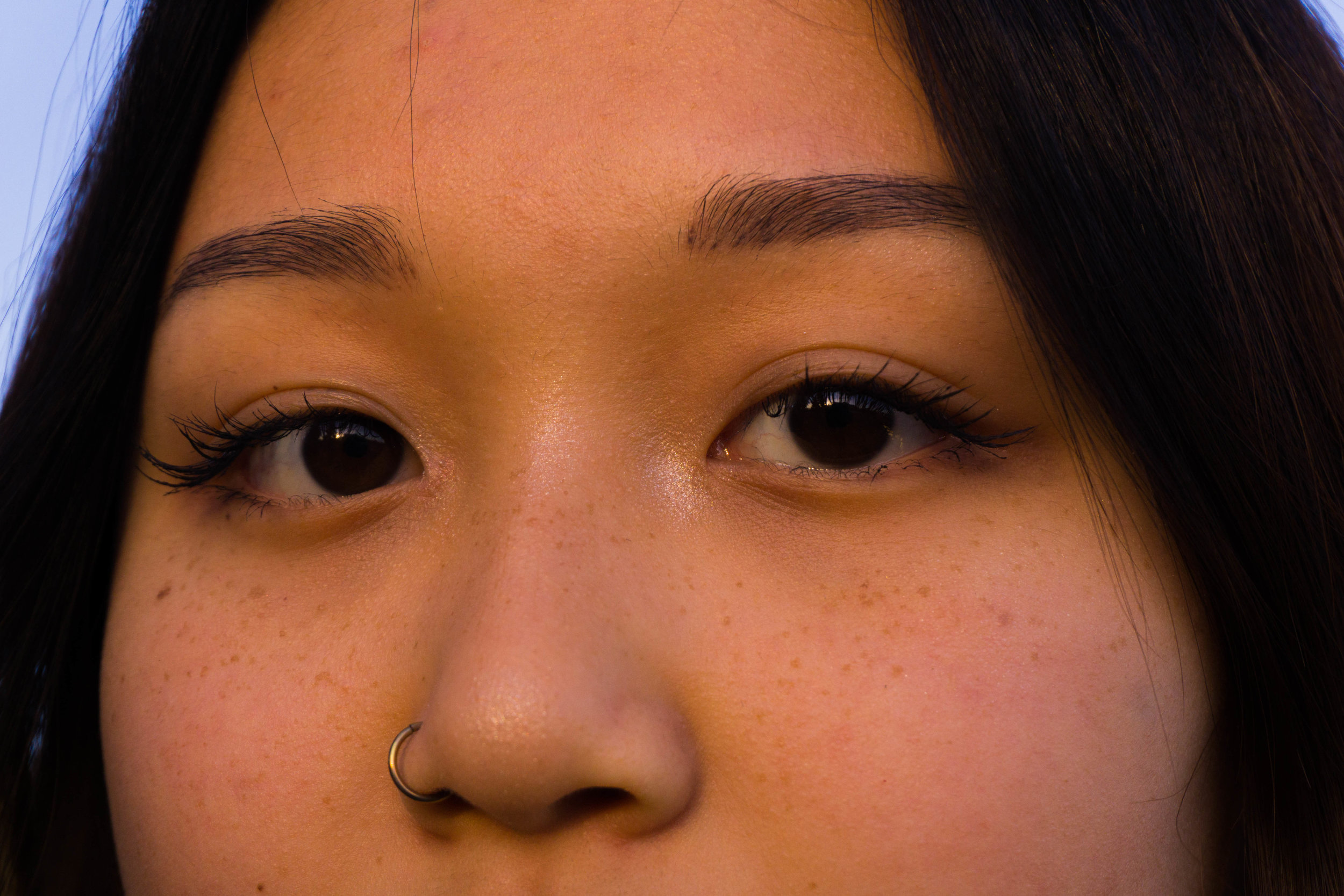 The same highlighter has been applied to the tip of the nose, the inner corner of the eyes, and the top corner of the brow bone where the eyebrow is angled.