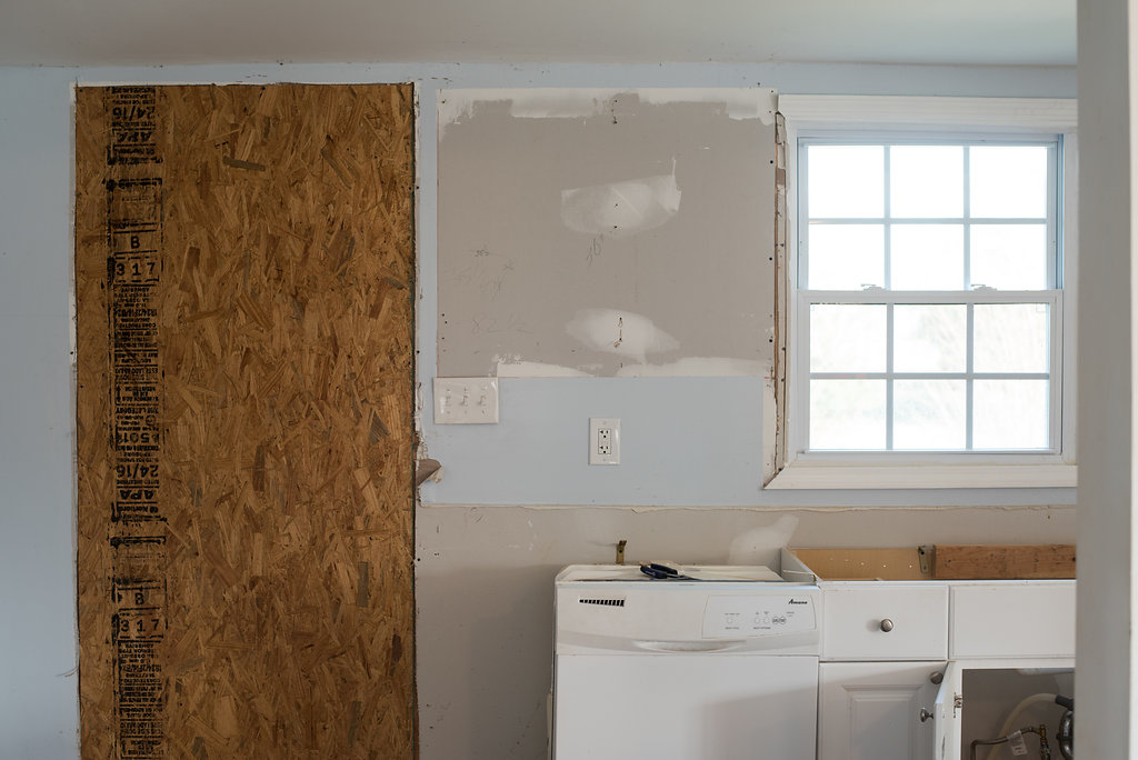 """The """"old"""" kitchen. A door use to be where this piece of plywood is. While one of the contractors thought I was nutes for closing it in, it was a happy day when the crew finally saw my vision!   PC: Emily Reedstrom"""