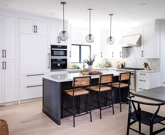 17TH AVE | We're so happy with how this high- contrast space came together and how the gray kitchen island with smoke glass pendants from @schoolhouse creates a unique focal point in this open-concept main floor. #md17thave