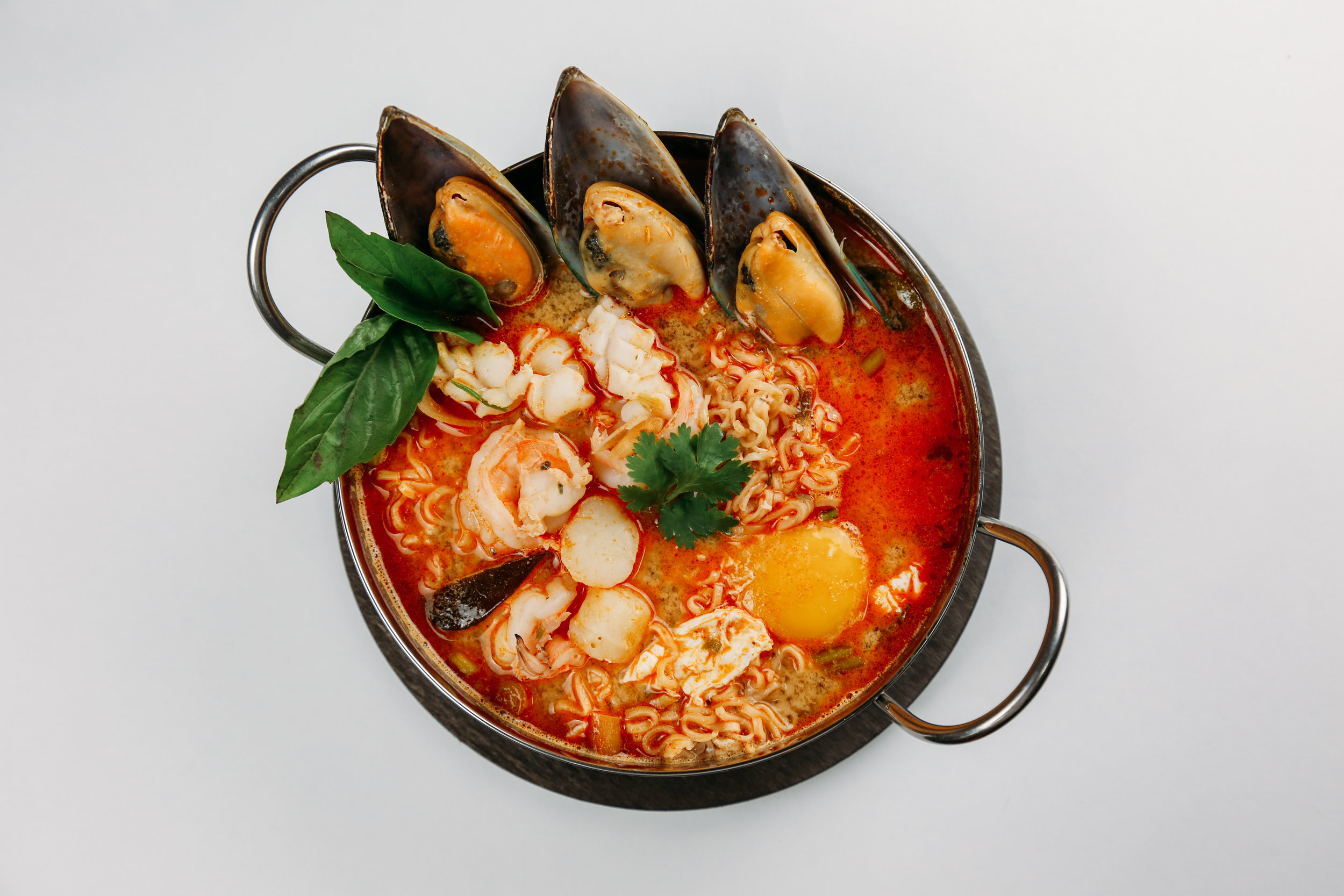 Tom Yum Noodle Soup - With scallion, chili, lemongrass,galanga,lime leaf in spicy Tom Yum brothtop with egg.
