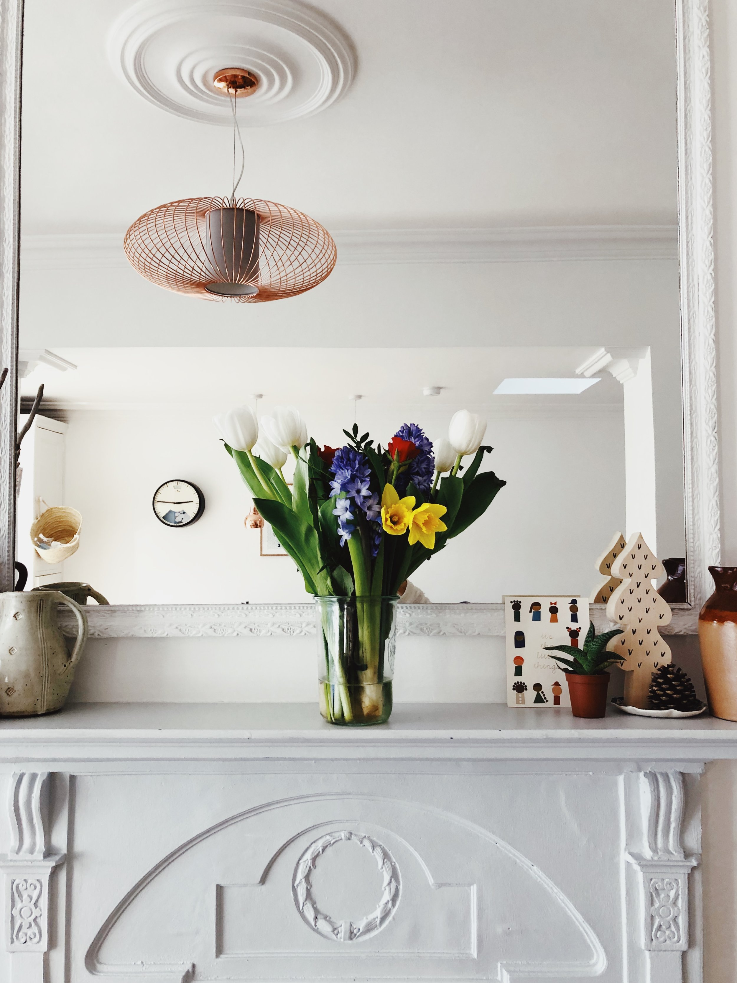 Flowers on a mantlepiece. Spring vignette. Spring cleaning. An essay on tidying up and tips to make spring cleaning easy. Decluttering practical life hacks. More on OurStoryTime.co.uk