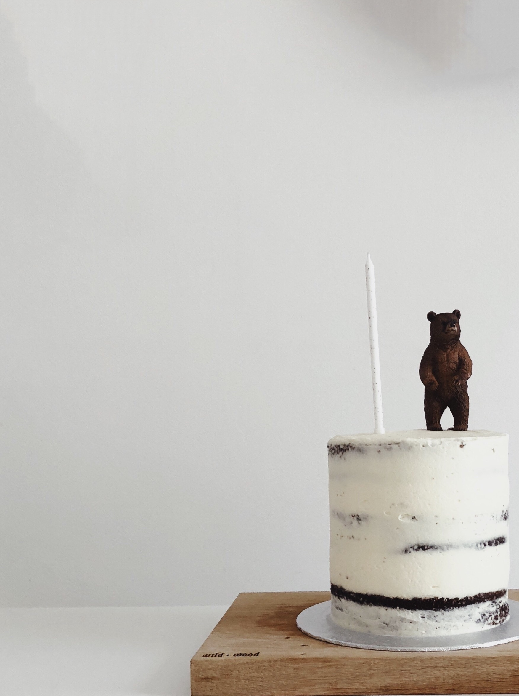 naked frosted cake with bear on top