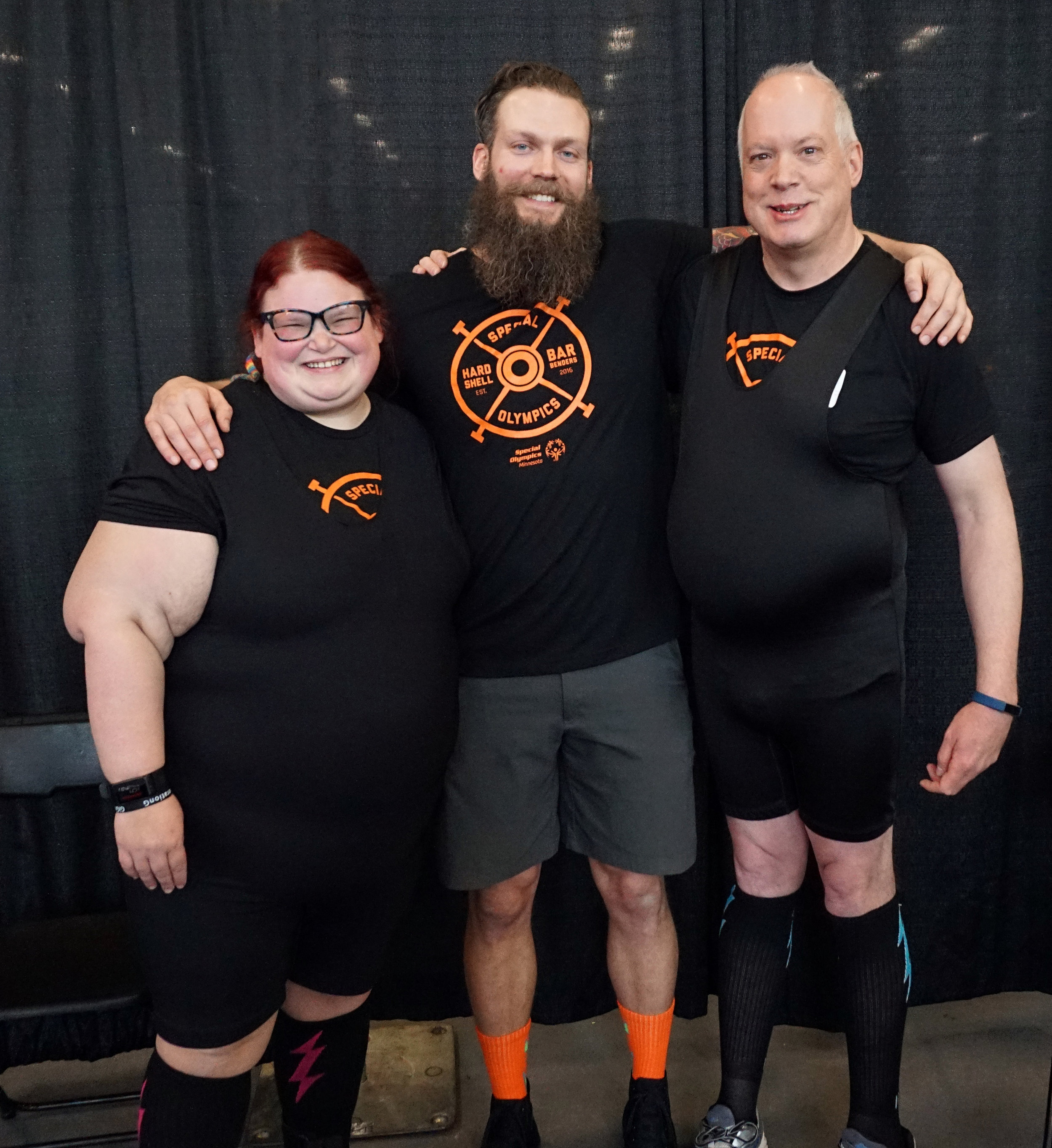 Photo: Three people, two men and one woman. Logo on their shirts reads Special Olympics HardShell Barbenders. From left to right: Nell, Ben and Dave at a Special Olympics Minnesota State Powerlifting meet.