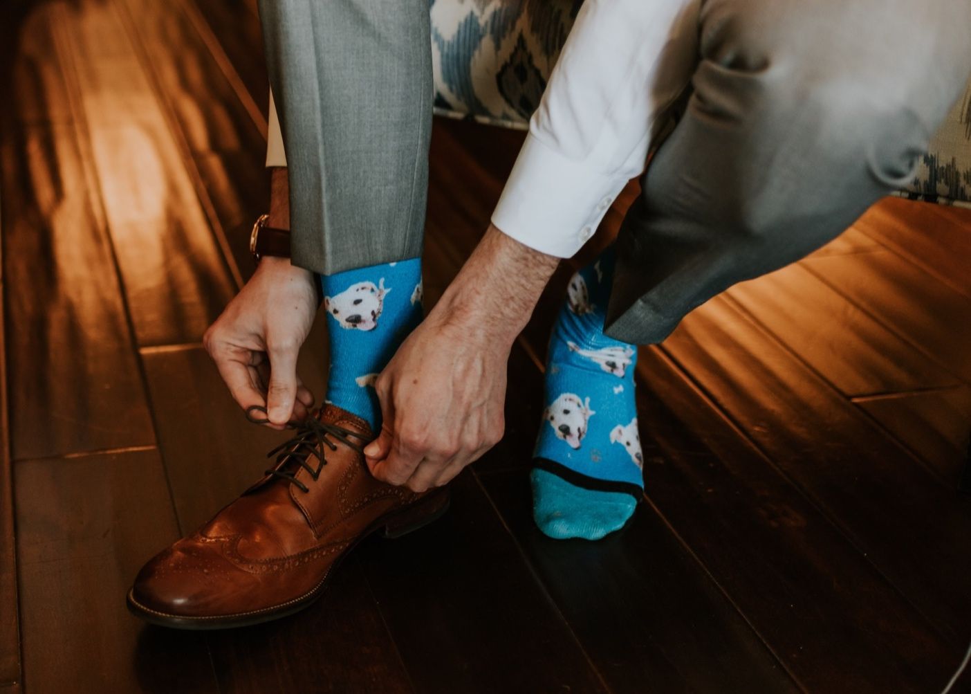 Groom putting on shoes. Groom personalized socks. Groom getting ready photos. Canary Hotel Santa Barbara.