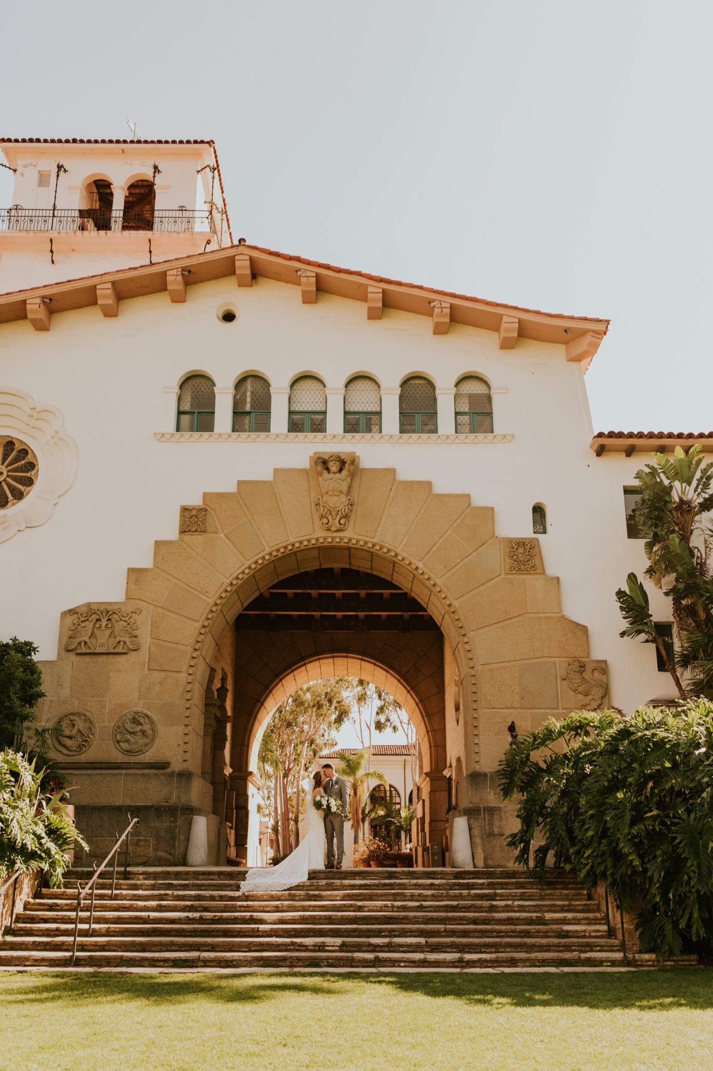 Santa Barbara Courthouse Wedding. Bride and Groom portrait on steps under arched entryway.