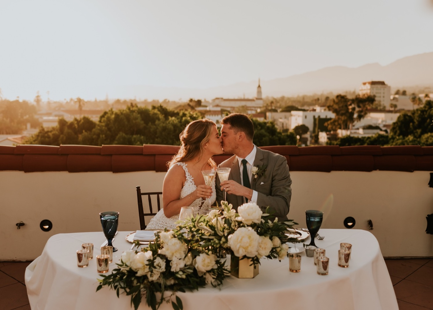Sunset Rooftop wedding reception Canary Hotel Santa Barbara. Bride and Groom kissing at sweetheart table.