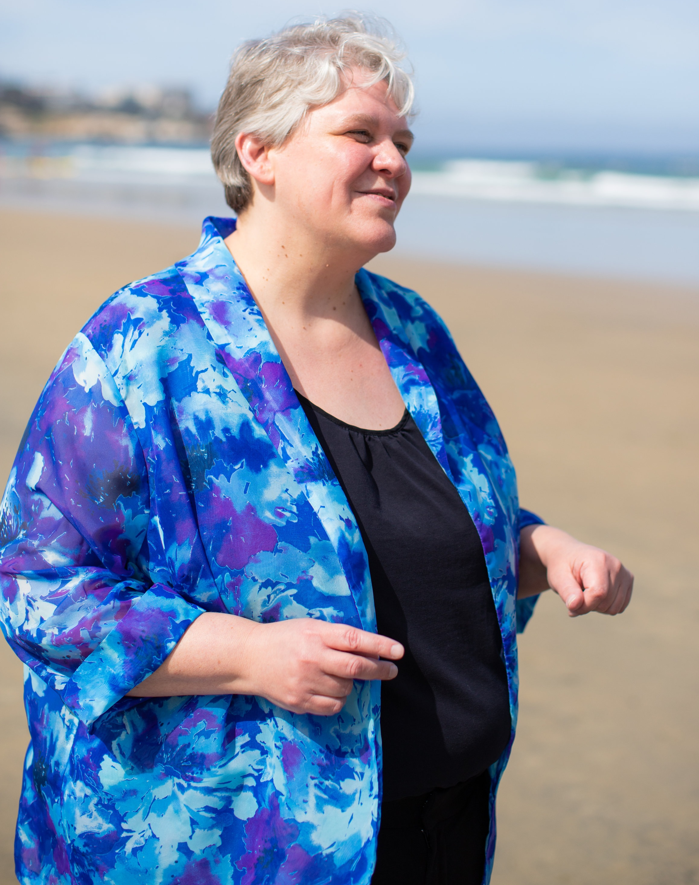 Your story is important to me. - The picture is of Dr. Camilla Williams, standing on the beach and wearing a blue and purple flowing jacket over a black shirt.
