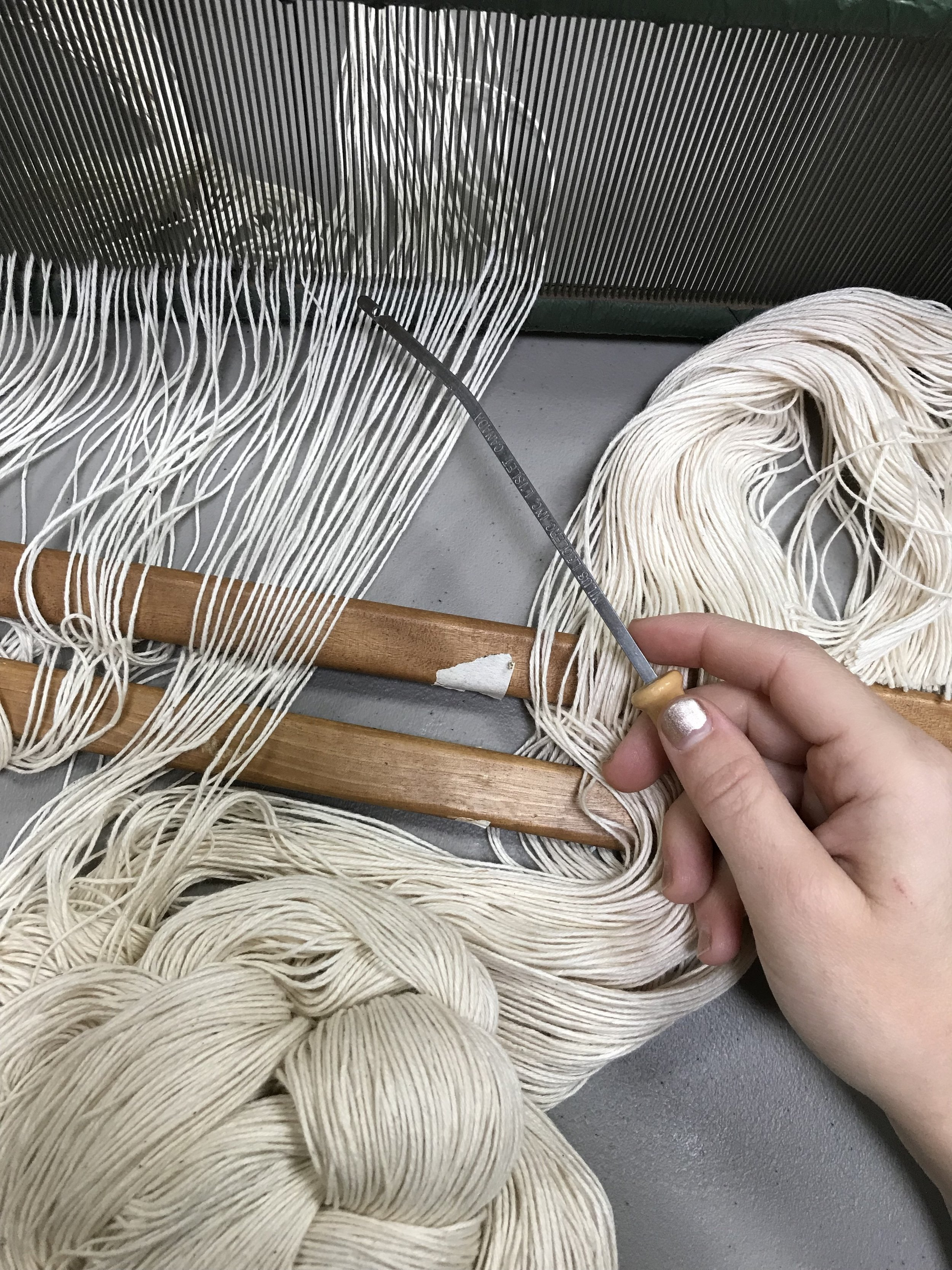 slowly pulling each thread through the reed