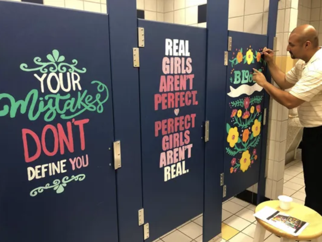 From Article: Principal Garcia adds finishing touches to one of the bathroom stalls.   (Photo: Courtesy Warren Middle School Forney ISD)
