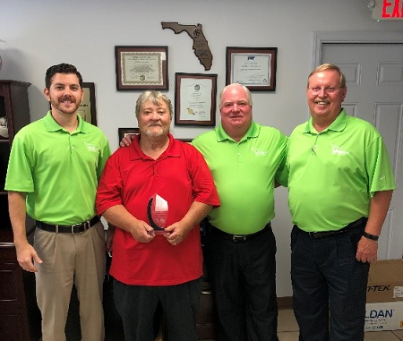 Wayne Hunt (second from left), independent auto dealer from Dothan, Alabama, was honored at Tallahassee Auto Auction's 35 Anniversary Celebration for 50 years in automotive sales. He is congratulated by members of the auction team (left to right): Tim Barry, Sales Representative, Eric Wagner, General Manager, and Mike Futrell, Sales Representative.
