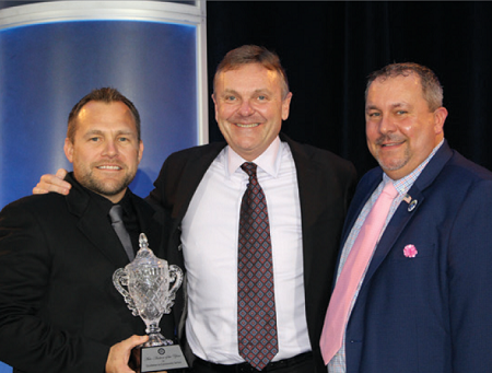 Luke Pidgeon (left), President of the NAAA Western Chapter, and NAAA President Chad Bailey (right), present Bob McConkey with NAAA's 2019 Auction of the Year Award for DAA Northwest.