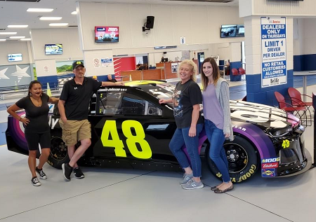 Bel Air Auto Auction employees Aria Gelina (left), Tracy Opper (2nd from right) and Melissa Penick (right), pause with Ally representative Bryan Hedge (2nd from left) for a photo with Ally's #48 Chevrolet Camaro ZL1.