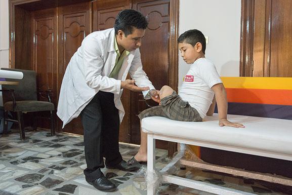 Eric Alvarez, Certified Prosthetic & Orthotic provider (CPO) evaluates Quasem, a Syrian refugees, for a new prosthetic leg.  photo: Stephen Petegorsky