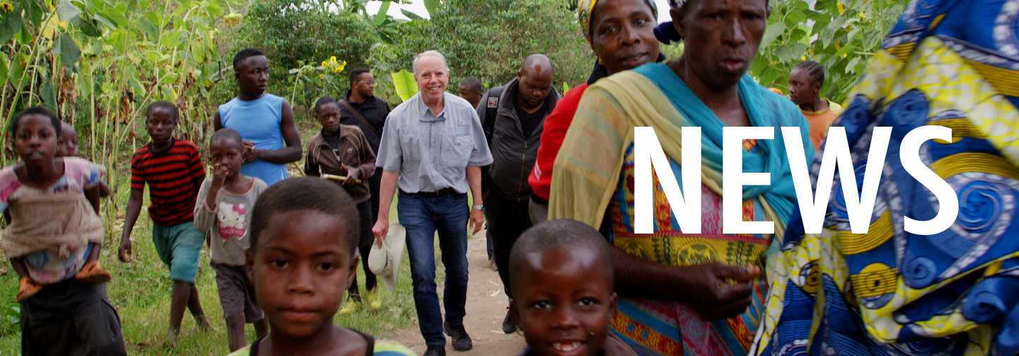News Banner is an image of Executive Director Michael Lundquist visiting a coffee growing community in the Democratic Republic of the congo. The image shows him walking on the road among a group of villagers of all ages