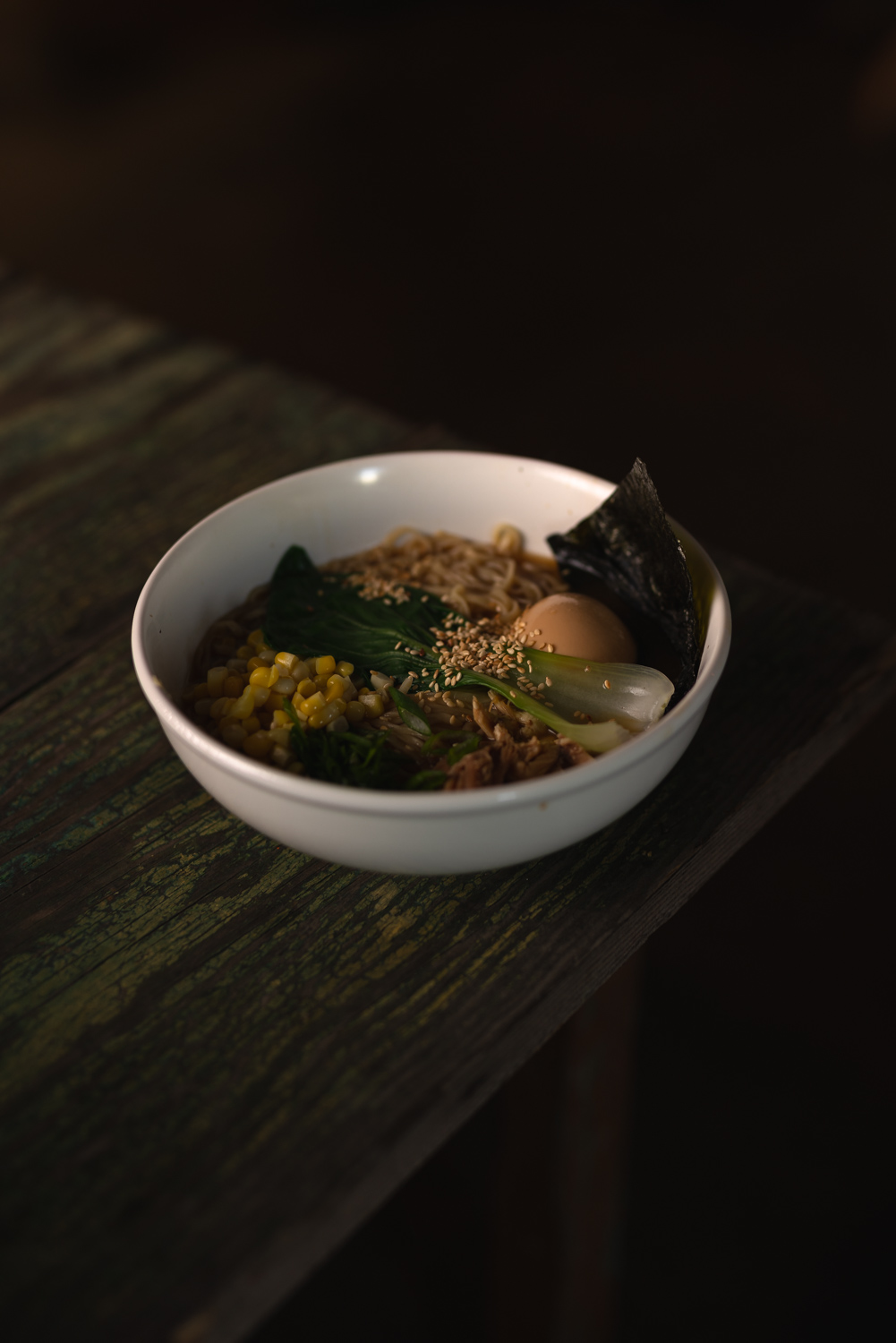 Shio ramen with seaweed, marinated egg, bok choy, corn, chicken, and toasted sesame seeds.