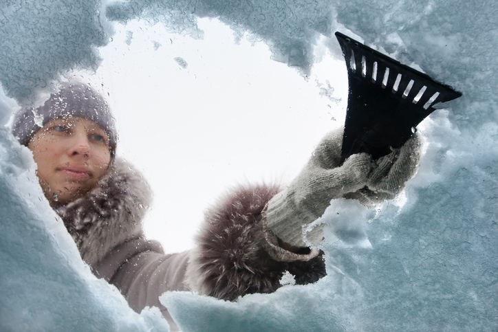 Woman Scraping Snow Off Car Window