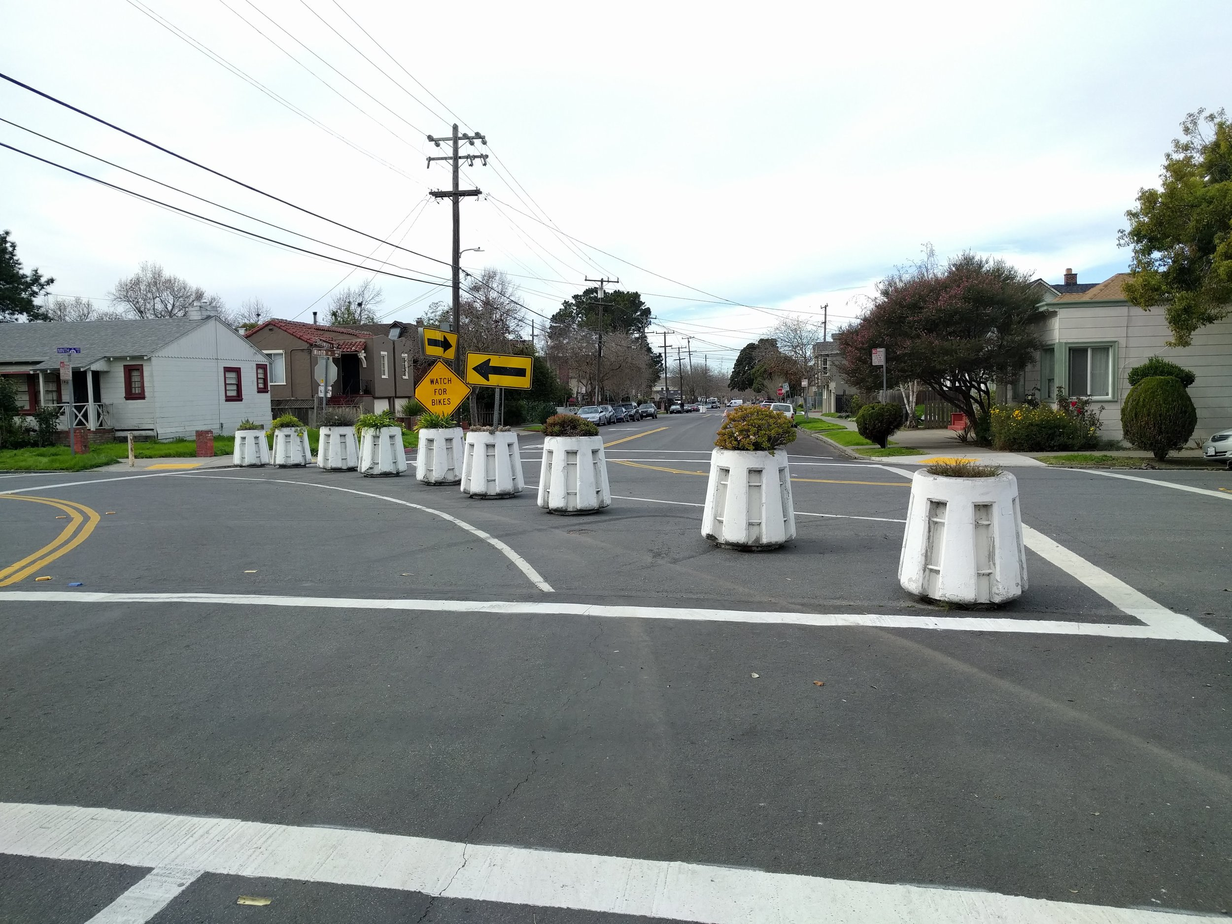 Here pictured:  the intersection of Delaware Street and 9th Street in West Berkeley. Cyclists can turn right onto 9th Street, a Bicycle Boulevard. The controversial traffic-calming project was initiated by the City of Berkeley in 1975 in order to keep cars out of residential neighborhoods.  Coupled with the Bicycle Boulevard Network, these barricades make bike commuting in Berkeley safe, efficient, and joyous.