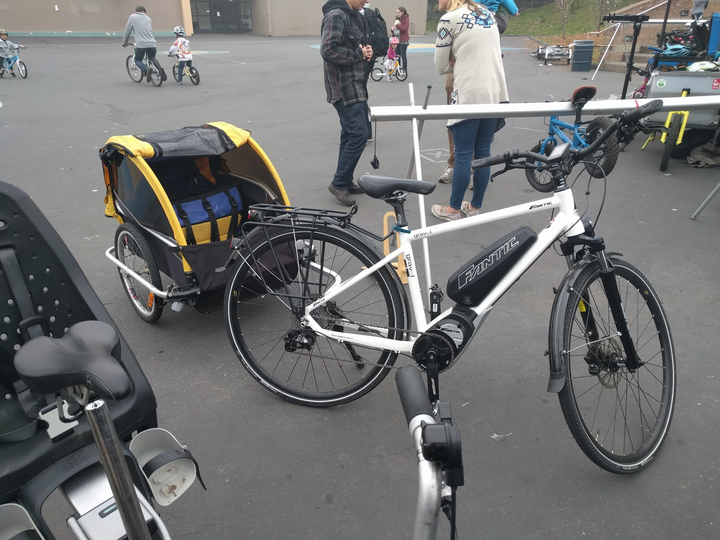 A two-kid trailer attached to a bike with electric-assist wheel and a front disc brake. This is well-suited to Bay Area hills!