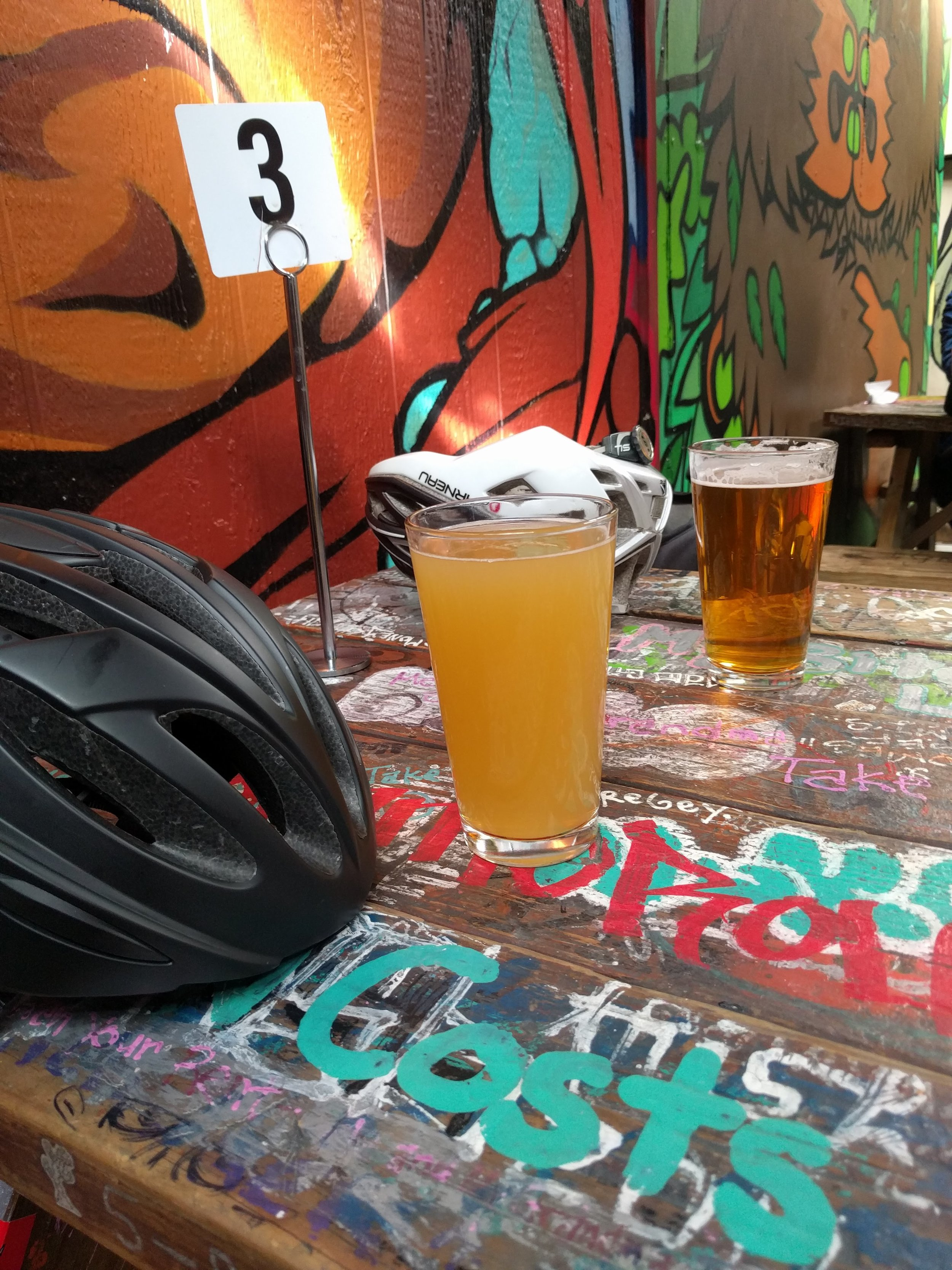 Pints, helmets, grungy tables, and burgers on the way. What more could you want from a Saturday afternoon?