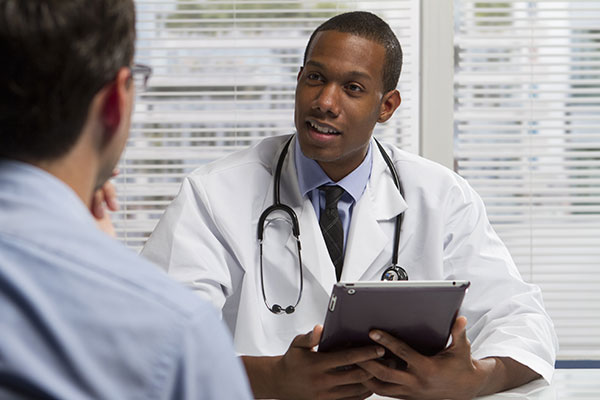 Doctor and Patient Speaking in Office with iPad