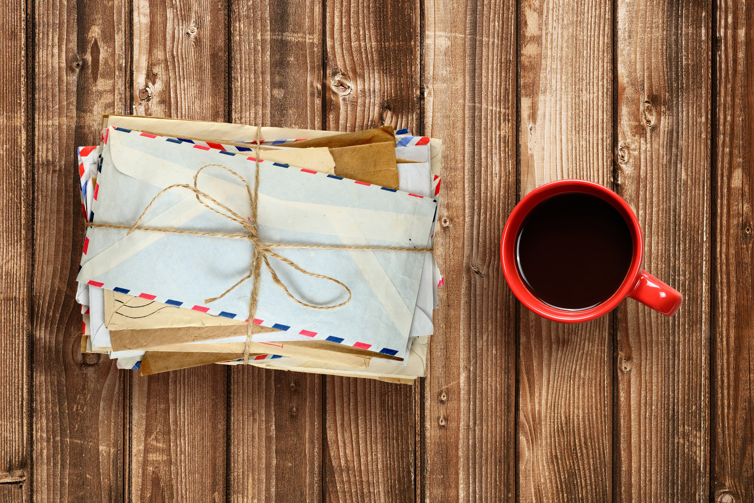 pile-of-old-envelopes-and-coffee-cup-on-wooden-P4QABRS.jpg