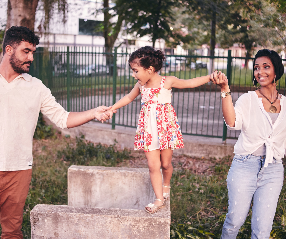 A mother and father playing with child in the park.