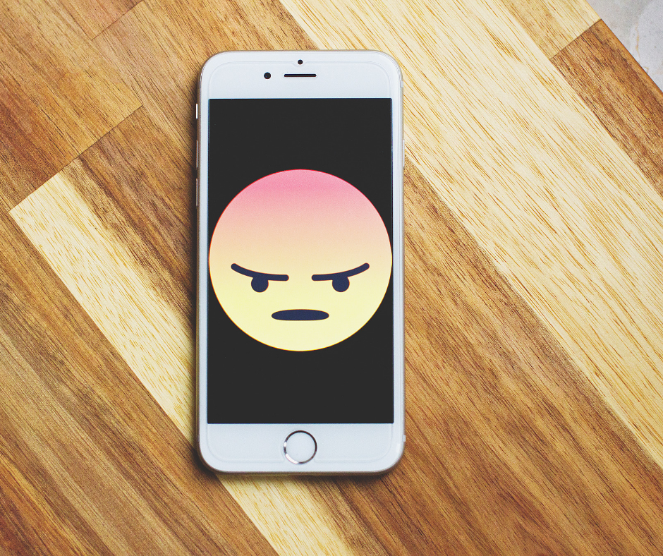 An angry face emoji on black background on smartphone on a wooden desk