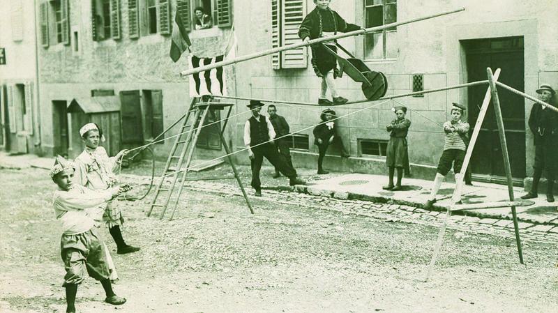 """Carte postale montrant des enfants chaux-de-fonniers imitant les """"danseurs de cordes"""" en 1909"""