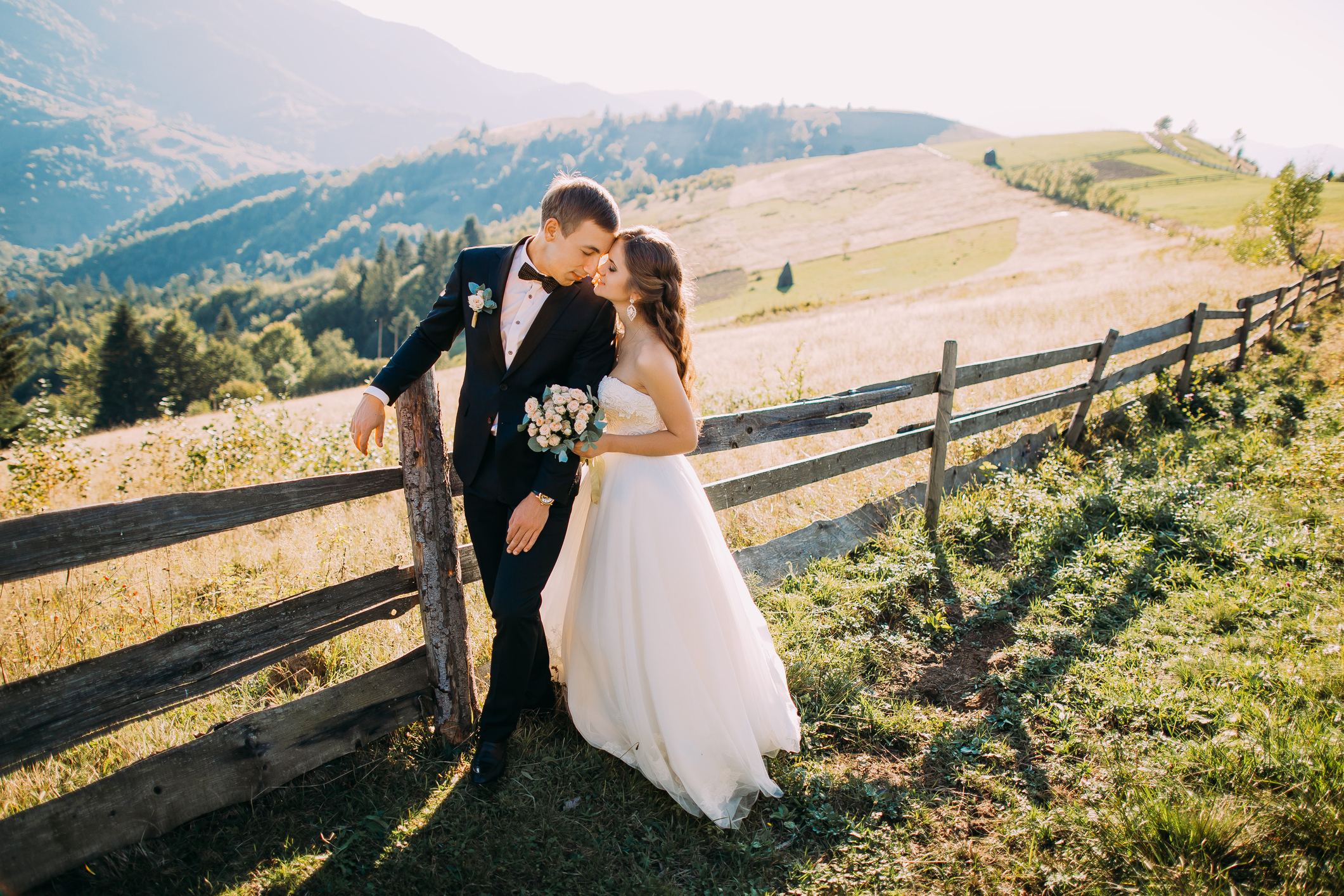 Bride-and-groom-standing-embracing-near-wooden-fence-on-the-526717136_2125x1417.jpeg