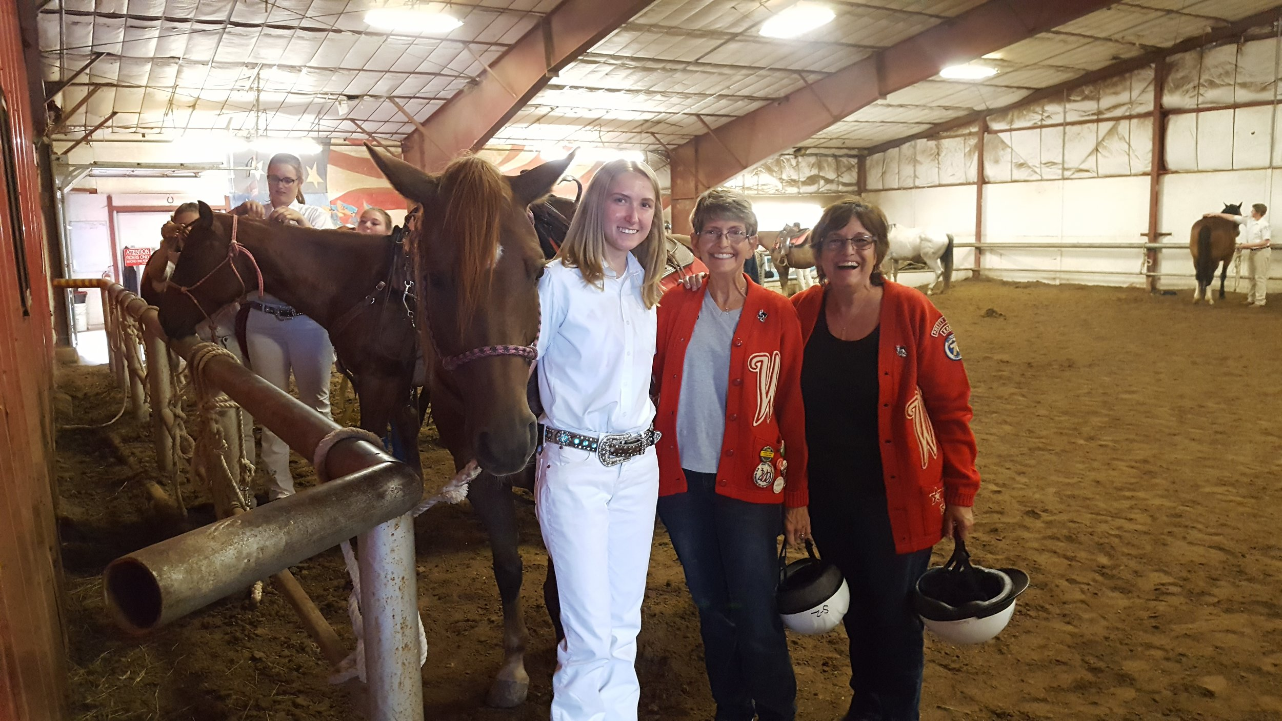Varsity Red Team senior Alexis Senecal and the Easley sisters tack-up Westernaire rental horse Dundee