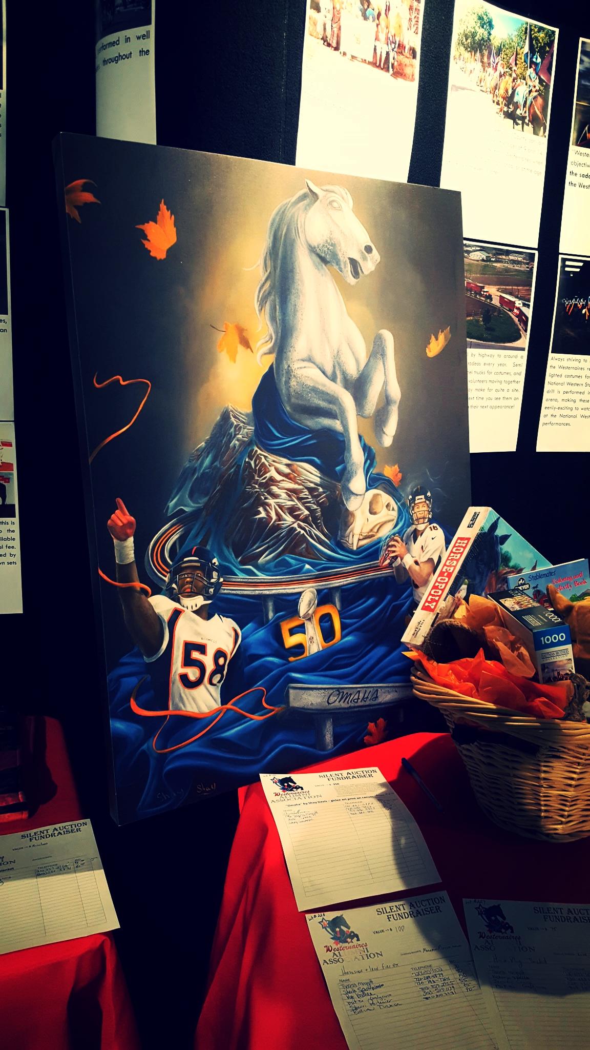 "Bidders plotted their strategy for obtaining Denver artist Shay Davis's giclee print, ""Omaha"", a surrealist homage to the Denver Broncos 2015-2016 Super Bowl season."