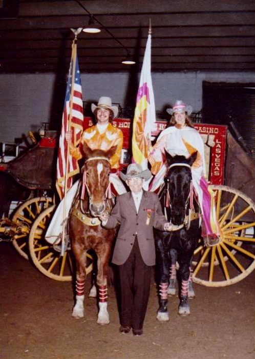 The 1982 Varsity Red Team Majors, Gary Feazell and Patty Miller, pose with Westernaires Founder and Director, Elmer E. Wyland, in the paddock of National Western Stock Show