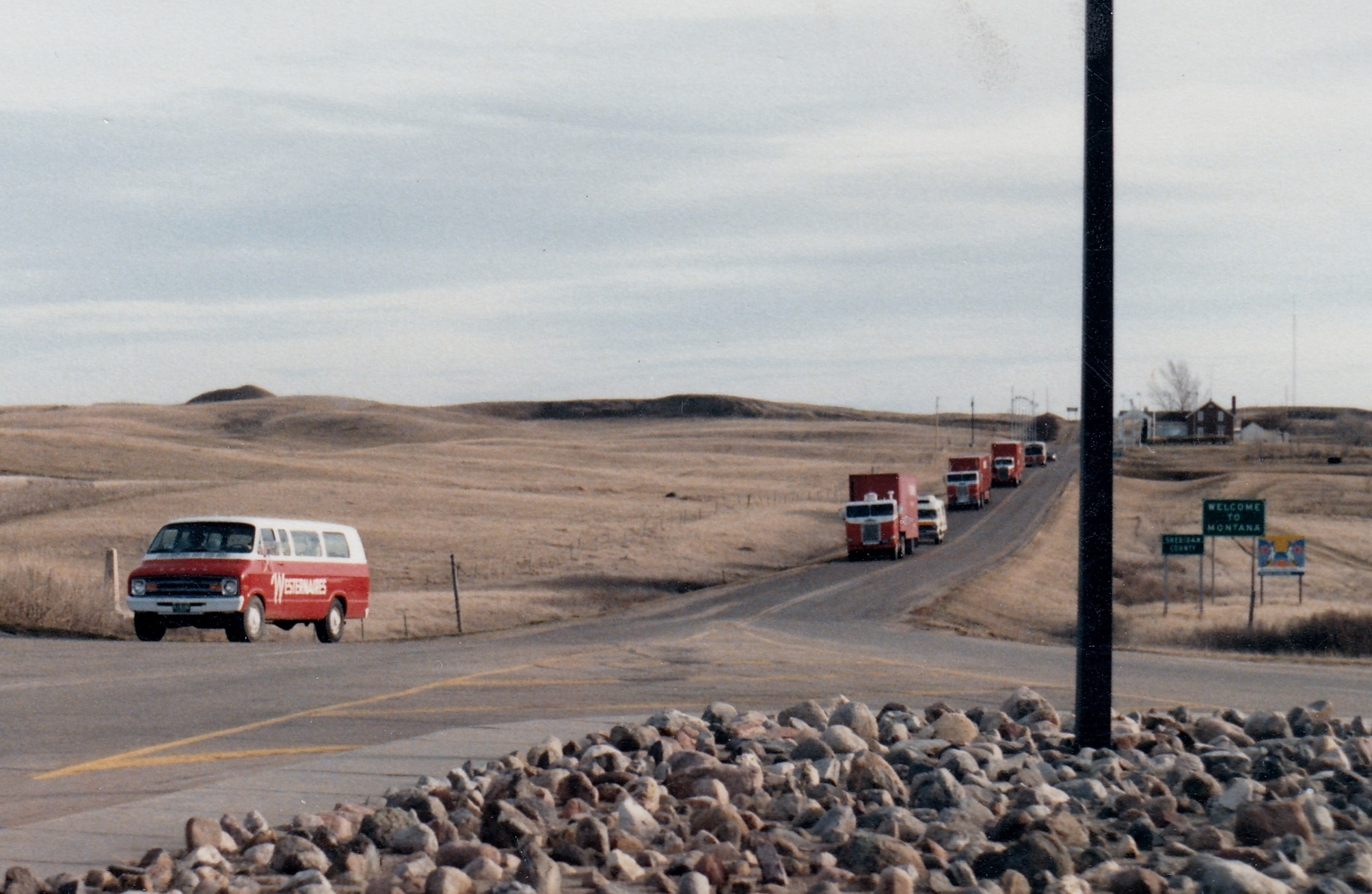 """The Westernaires convoy heads southbound across the Canadian/U.S. border and into Montana, March of 1986. Border agents (who were likely unaccustomed to seeing dozens of teenagers and their horses crossing the border) decided to be a bit difficult and required that every horse be unloaded from the horse vans. Satisfied after their inspection, the horses were quickly reloaded. The border agents were reportedly """"amazed""""at the organization and ease by which the Westernaires could load their horses onto the semis."""