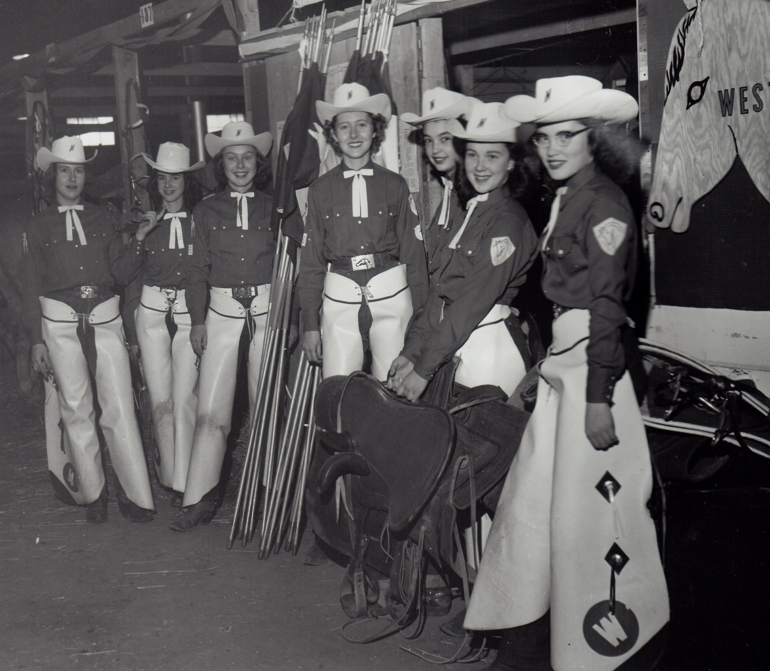Westernaire riders prepare themselves in the barn at National Western Stock Show in 1956. Performing first in the rodeo's Grand Entry, many of them would perform again in the Golden Sidesaddle Review act. The Westernaires Cavalry team also performed in select rodeos of the 1956 National Western.