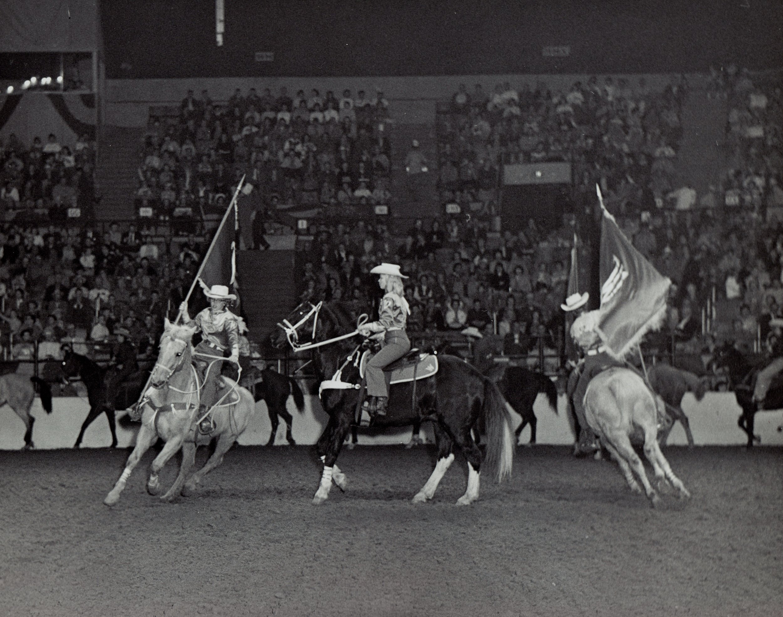 """Patty Hinshaw and """"Apache"""" the trick horse walk up the center of the arena as the Westernaires Grand Entry riders do-si-do around them."""