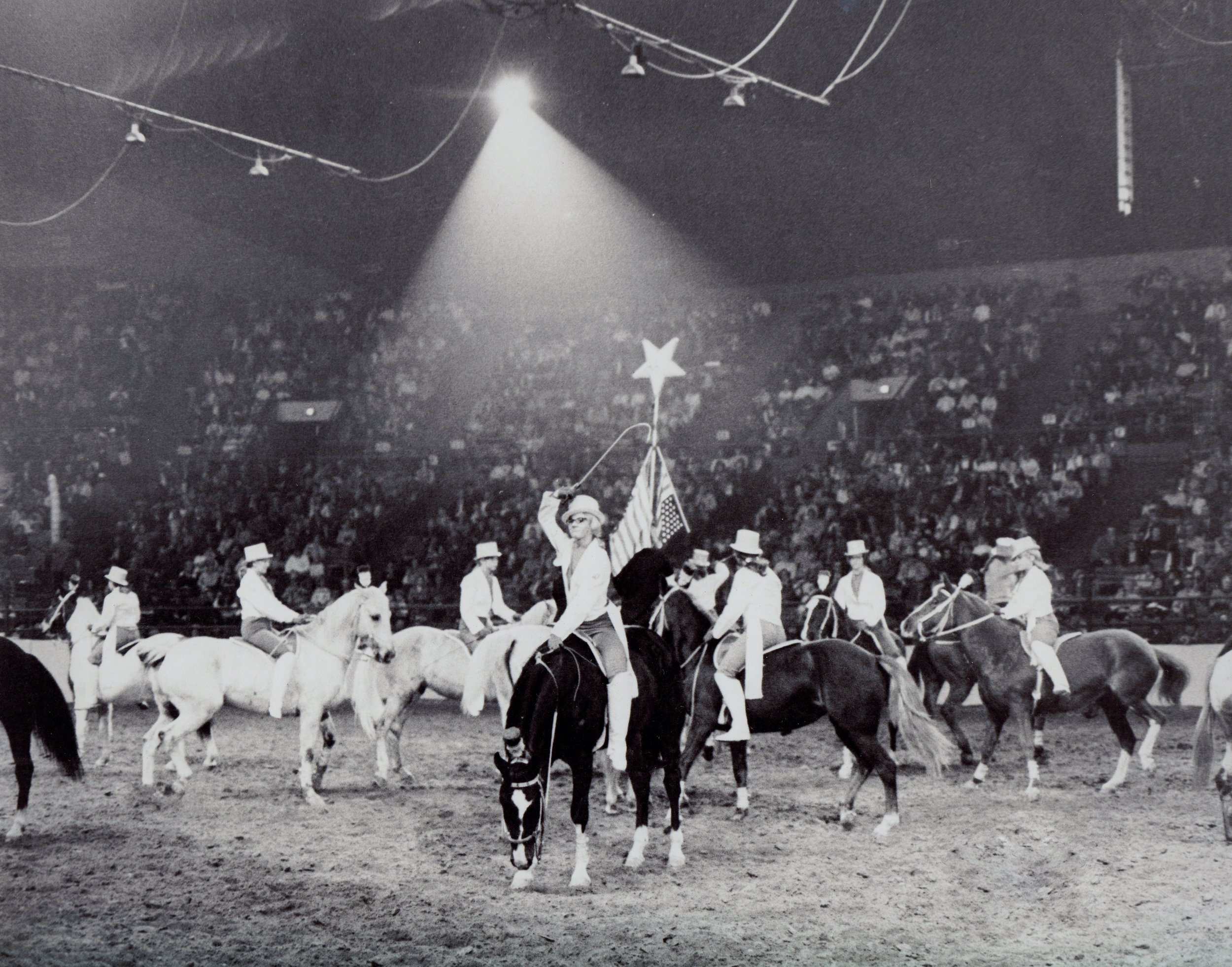 Melodie Mundell salutes the National Western Stock Show crowd during the 1969 exhibition of the dressage riders of Westernaires.
