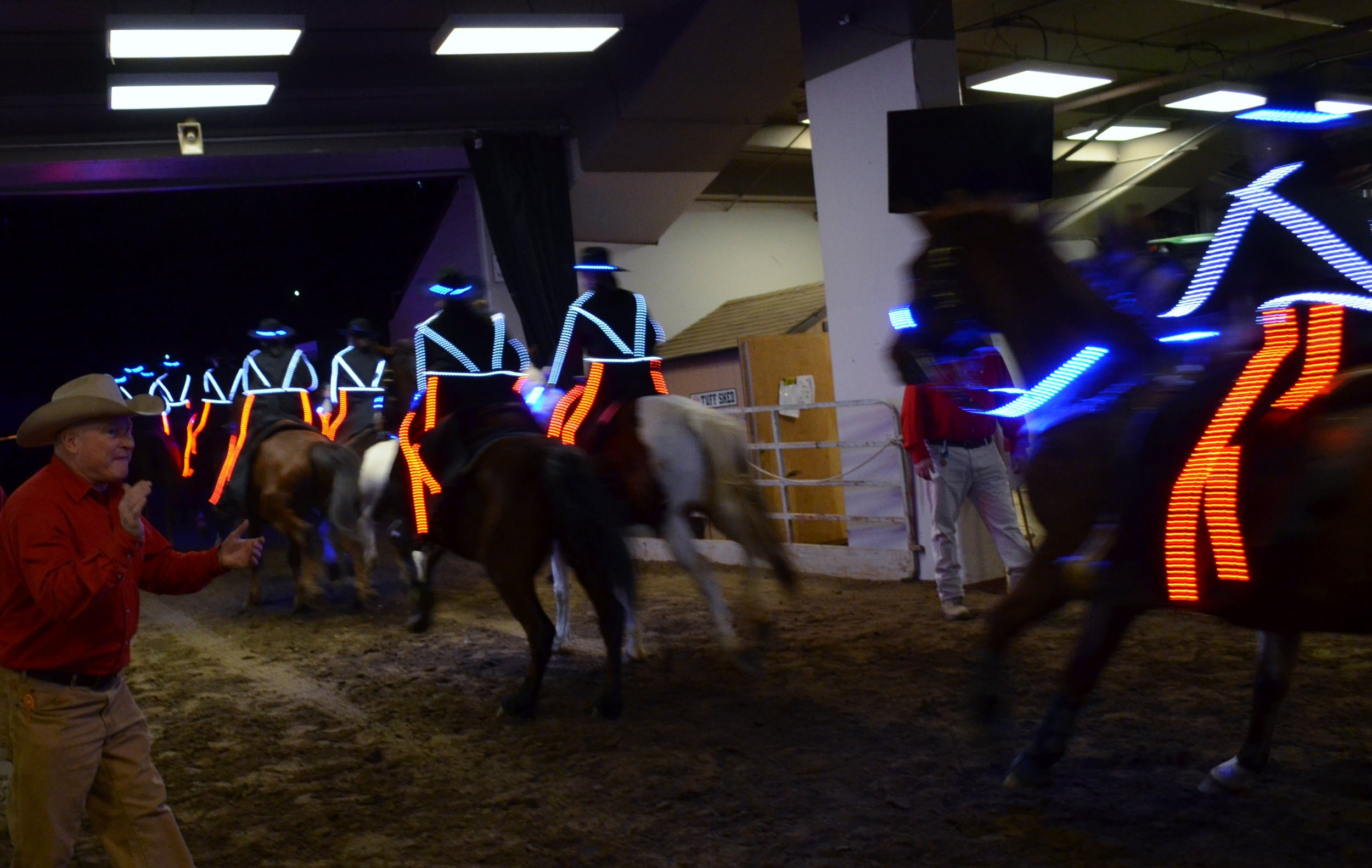 The Westernaires lighted Grand Entry team, in their 3rd generation costumes, dash through the gate and into the arena at the 2016 National Western Stock Show.