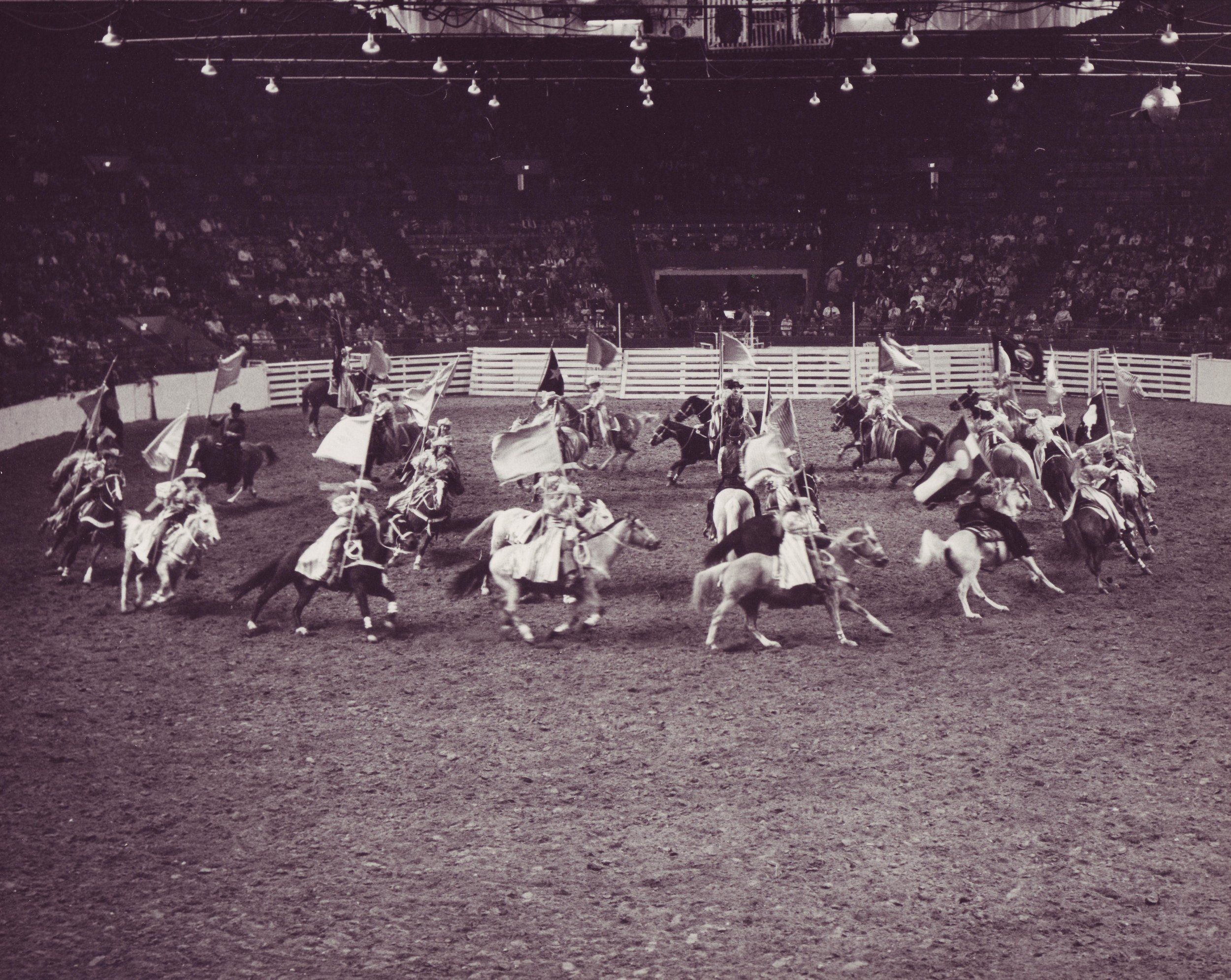 "Varsity Big Red Team performs their ""Corkscrew"" maneuver at the 1967 National Western Stock Show."