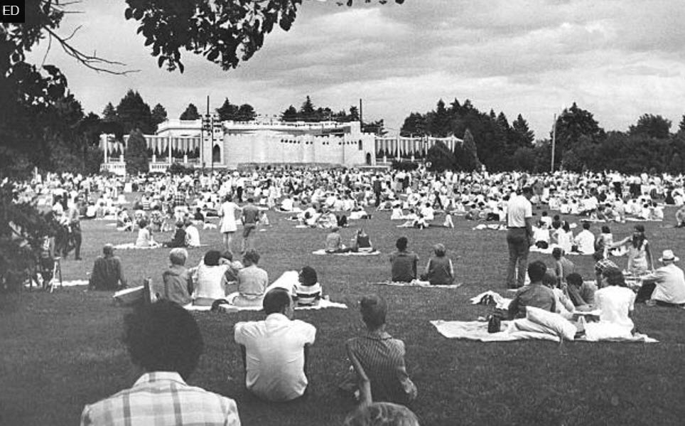"""Denver Opera Foundation's 1969 production of  Camelot , in Denver's Cheesman Park. The elaborate set built around the park's pavilion was designed to look like Camelot castle, replete with towers, a gatehouse, and drawbridges over the orchestra pit """"moat"""".  An estimated 8,000 people attended the production of  Camelot  on Tuesday night alone. Many brought picnic fare and enjoyed the opera from the ground."""