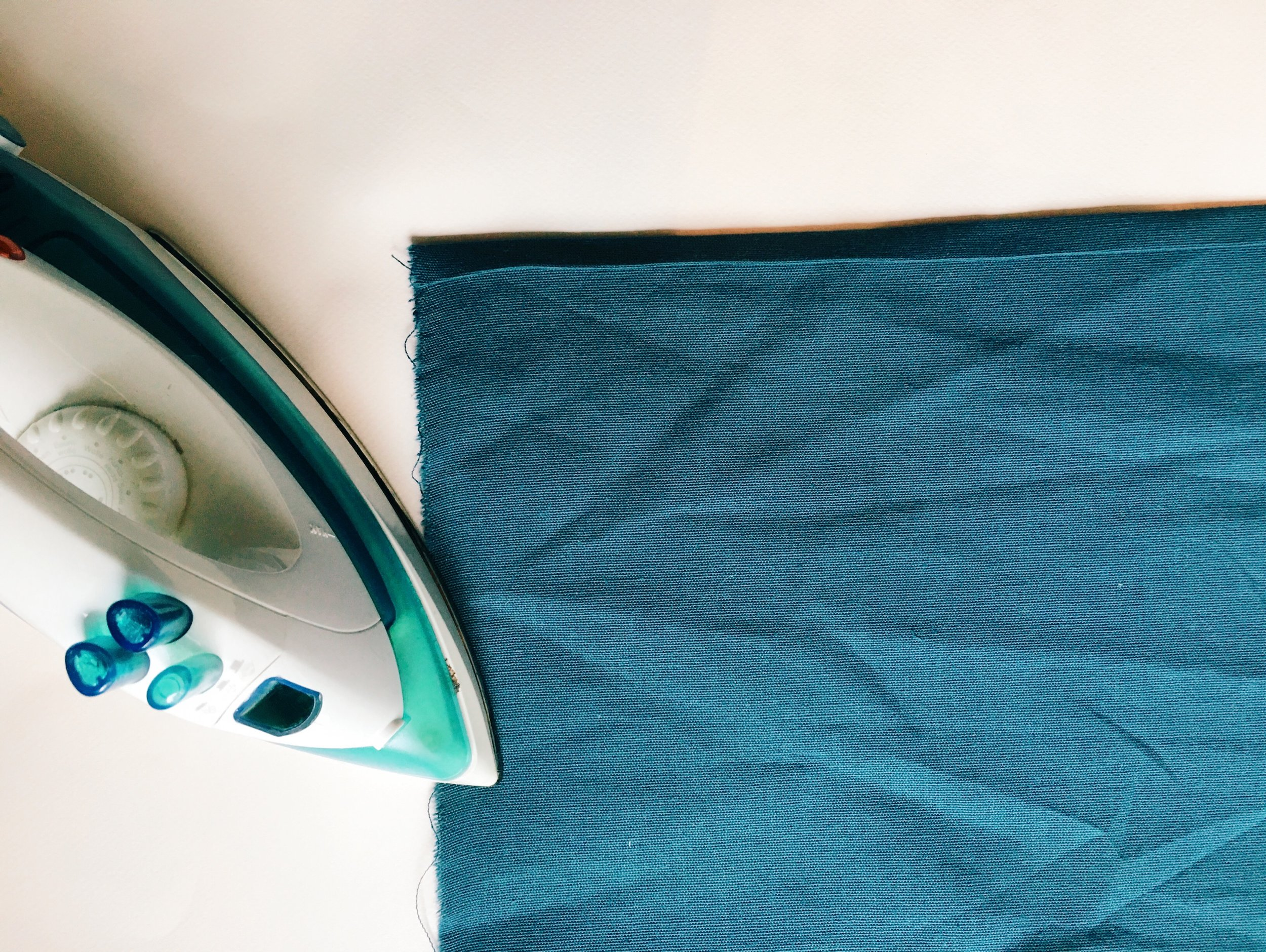 Fold and press the hem on one long side of both back pieces.