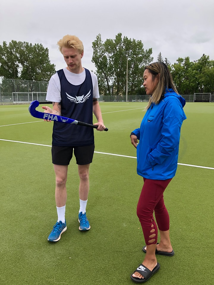 Thu showing teaching Matt about the different ways the field hockey stick can be used.