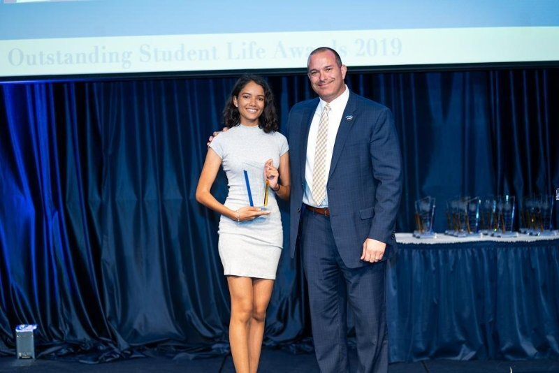 Afsaana Kiara Mohammed receives an award on behalf of her organization, the Born Different Advocate Alliance, which honored its efforts in creating a more inclusive environment on campus and help connect disabled students with equal educational and career-related opportunities.