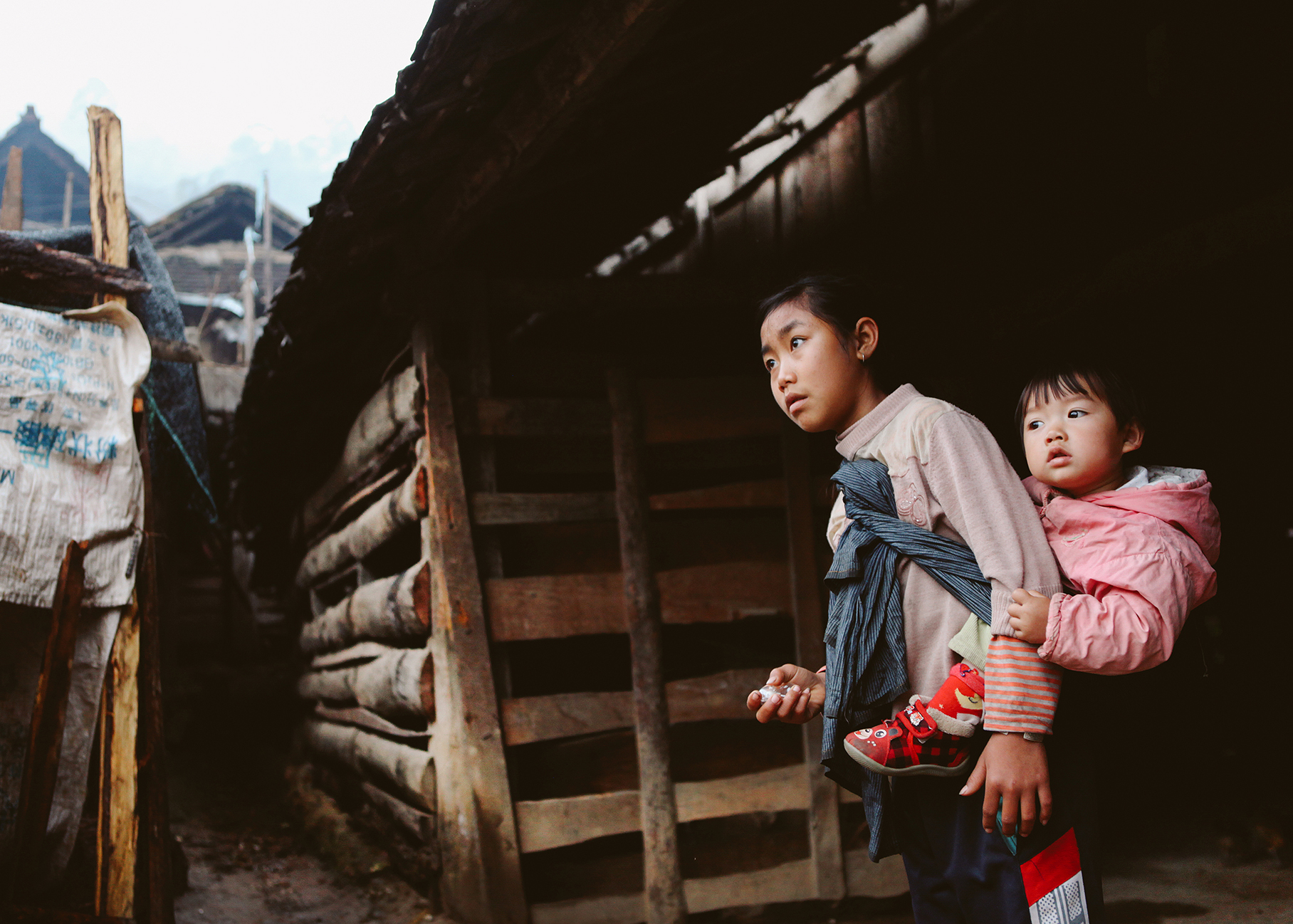 Girl looking after sister, Man Noi, China