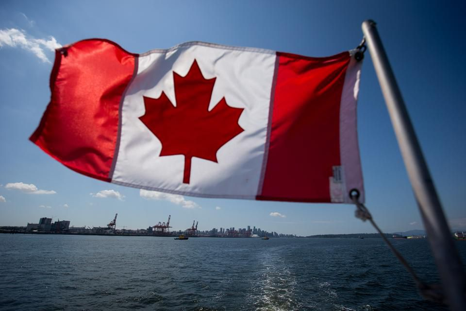 A Canadian flag flies from a Harbour Authority patrol boat as gantry cranes are seen at the Port of Vancouver in Vancouver, British Columbia, Canada. (Credit: Darryl Dyck/Bloomberg)