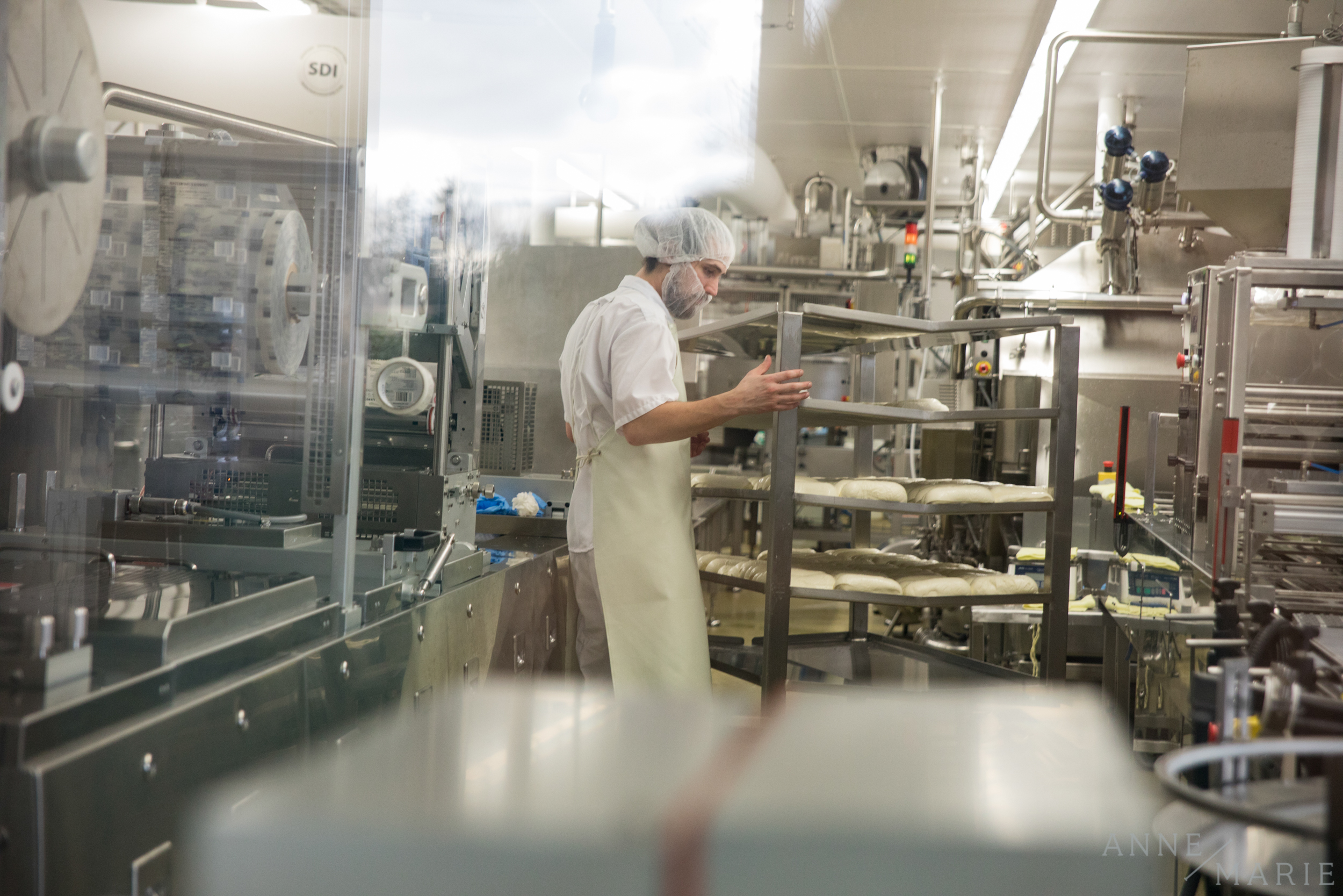 One of the employees moves some of the fresh cheese.